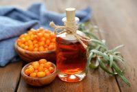 Havtornsolja i flaska och havtornsbär i skål bredvid. För friska urinvägar hos katter.