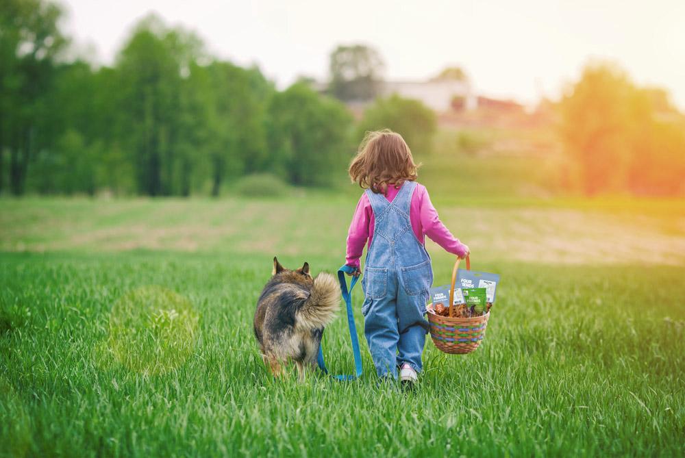 Liten flicka som leder en hund i koppel över en äng i solnedgång, med en korg fylld med FourFriendsprodukter i ena handen.