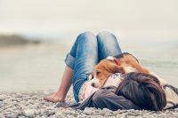 Hund som ligger på mattes mage vid en stenig strand.